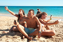 Group of teenagers in the beach with cellphones